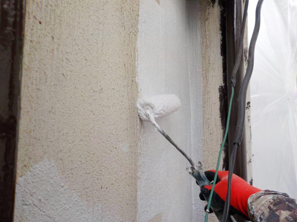 外壁を塗装する手
