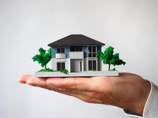 外壁の耐用年数 家の模型を持つ手